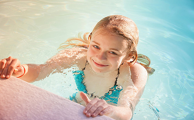 Beautiful teenage blond girl swims in outdoor pool, closeup summer portrait, colorful toned photo, old style instagram filter effect