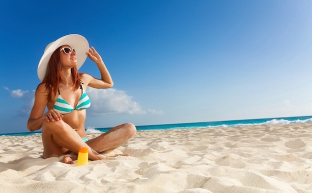 Slim girl in blue striped bikini on seashore