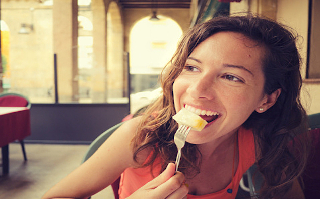 Happy woman eating some fruit